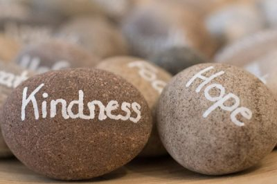 A collection of stones with words written upon them. the ones readable say kindness and hope
